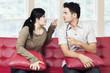 Couple quarreling while sitting on sofa