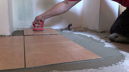 Handyman worker place floor tiles with special tool