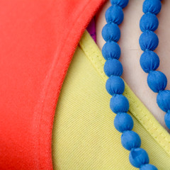Blue necklace with yellow top and red cardigan
