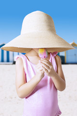 Girl with hat eating ice cream at coast