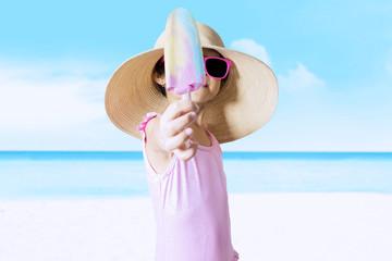 Happy child showing ice cream at coast