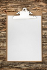 Notepad. Clipboard with a blank sheet of paper on wooden table