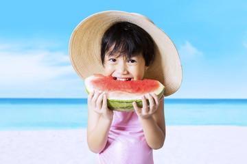 Happy kid eats watermelon at coast