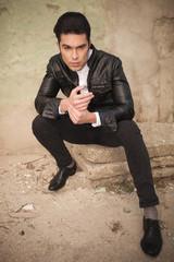 handsome young fashion man sitting near a wall