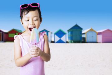 Joyful kid bite ice cream at coast