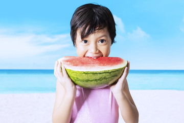 Kid eats watermelon on the beach
