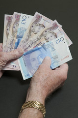 Hands holding bank notes from Gibraltar
