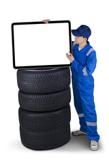 Mechanic with a billboard above tires