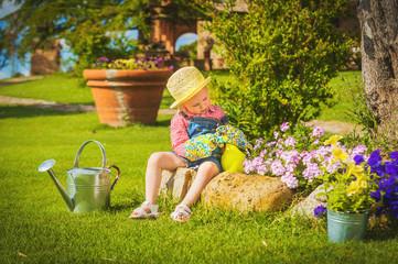 Cute little girl doing garden work between colorful flowers.