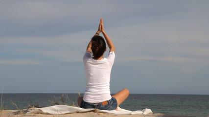 Woman doing yoga on the coast of the sea
