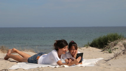 Mother and daughter sitting on the beach and using tablet