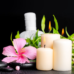 spa setting of hibiscus flower, twig bamboo, thai herbal compres