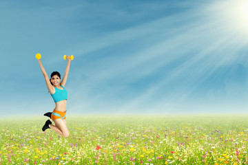 Woman jumping with dumbbells