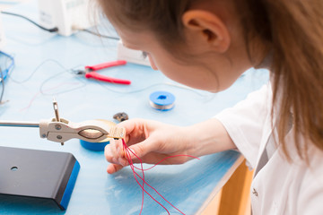 Young woman assemble optic sensor for intelligent robot system