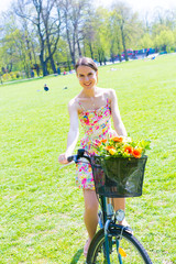 Young woman in short colorful dress with long hair rides a bicyc