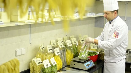 chef puts dried pasta into bags - factory