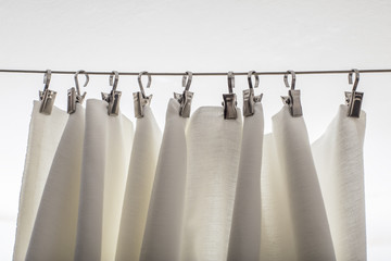 cream-colored curtain hanging on a string on metal hooks