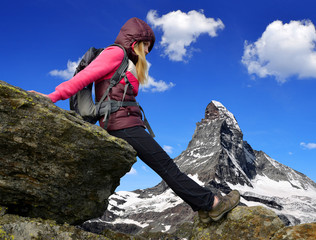 Girl on rock, in the background mount Matterhorn - Swiss Alps
