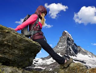 Girl on rock, in the background mount Matterhorn - Swiss Alps