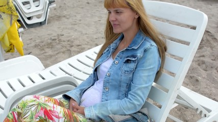 Pregnant woman sitting on the chair by the sea