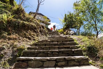 Hikers ascending a long and steep flight of steps in Nepal