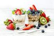 Leinwandbild Motiv Healthy breakfast with muesli in glass, fresh berries and yogurt