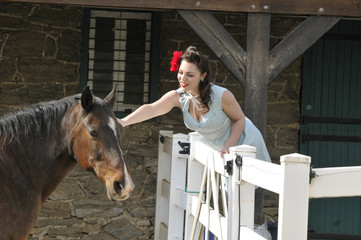 pin up girl petting a horse on a farm