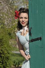 pin up girl peeking behind a green barn  door