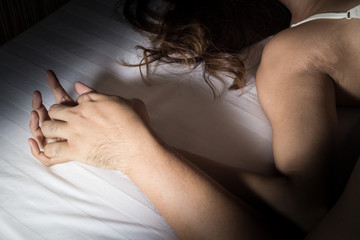 Man and woman hand in sex relationship on bed.