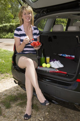 Woman with strawberries sitting on trunk of car