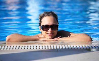 Smiling girl in swimming pool. Resort