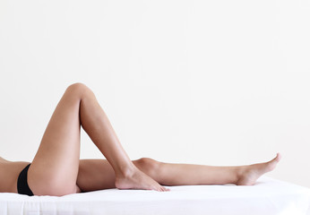 Nude woman with beautiful legs lying on bed