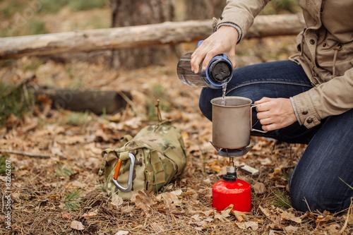 Keuken foto achterwand Kamperen woman pours water from a bottle into a mug