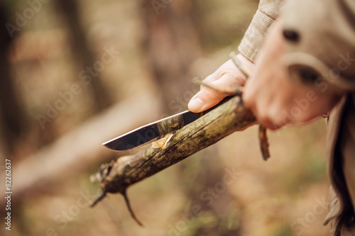 Tuinposter Kamperen Girl cuts a stick a knife