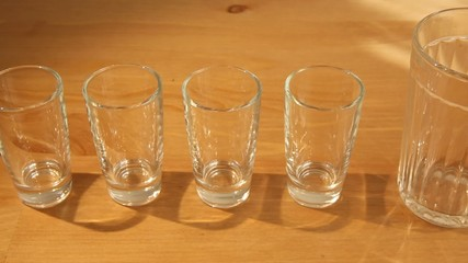 A row of small wine glasses with a big one in the middle