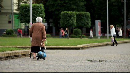 Old woman walking with stick and shopping cart down the street