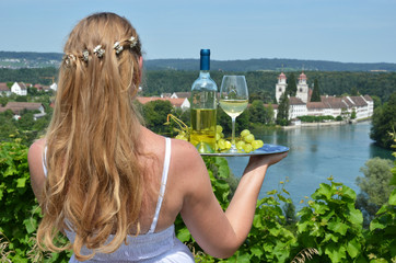 Girl holding wine and grapes on the plate. Vineyards of Rheinau,