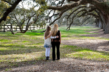 Mother and daughter walking in the park.
