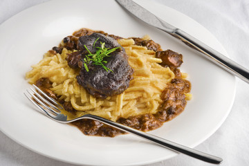 Slow cooked pork cheeks in gravy with spaetzle noodles
