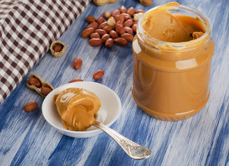 Peanut butter in  spoon  with peanuts.