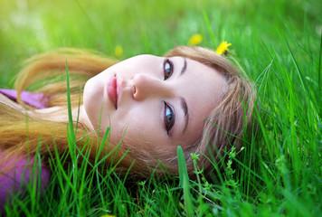 Beautiful girl relaxing lying on the grass in the garden.