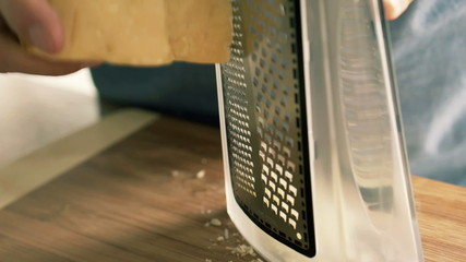 Closeup of man grating cheese on grater in kitchen