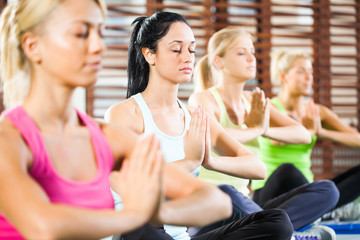 Four girls meditating after fitness training in gym