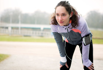 Young attractive woman stretching after a running session