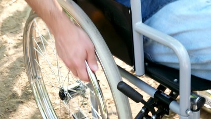 Detail of a man moving on a wheelchair