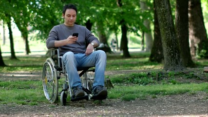 Portrait of a disabled man using his smartphone in a park