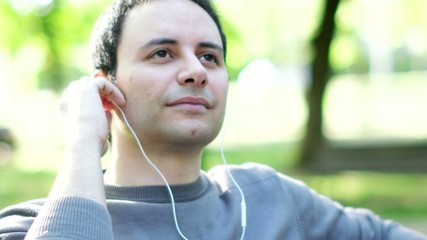 Portrait of a man listening music in a park