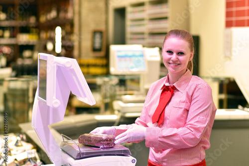 junge Verkäuferin an der Fleischtheke im Supermarkt - 82286695