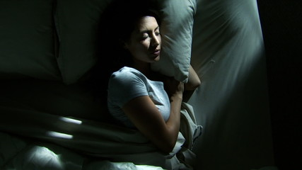 Restless woman in bed at night