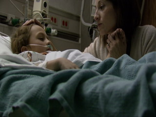 Mother comforting child in hospital bed
